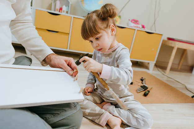 Little 4-years girl helping her father assemble the kids bed using small hammer in the kids bedroom.
