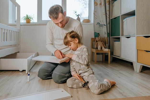 Маленькая 4-летняя девочка помогает своему отцу собирать или ремонтировать ящик современной детской кровати в форме домика в детской спальне.