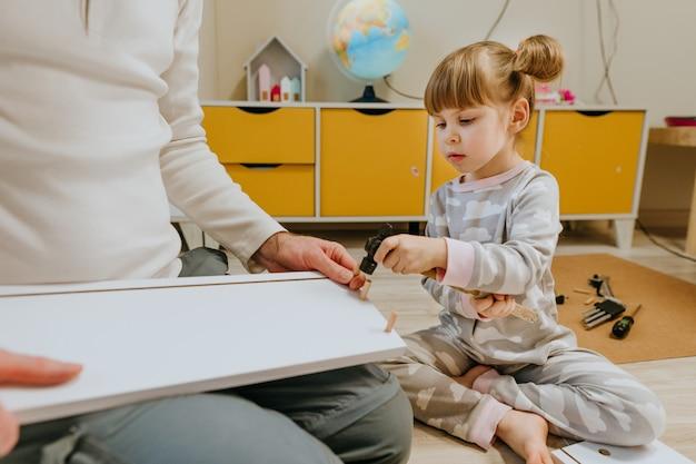 父親が子供の寝室で小さなハンマーを使って子供のベッドを組み立てるのを手伝っている4歳の少女。