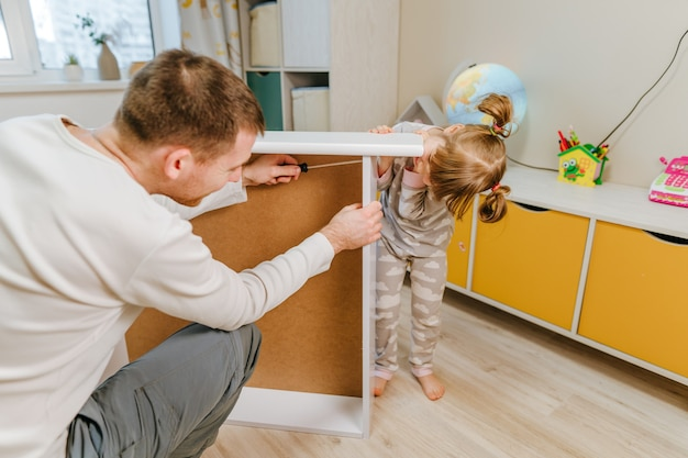 Little 4-years girl helps her father assemble or fixing the drawer of bed in the kids bedroom.