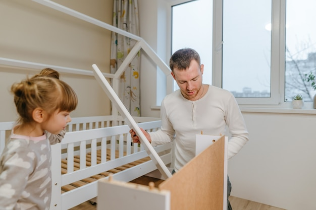 Маленькая 4-летняя девочка помогает отцу собрать или починить ящик кровати в детской спальне.