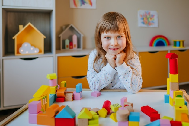 Little 4 years old girl playing with wooden cubes building a toy city