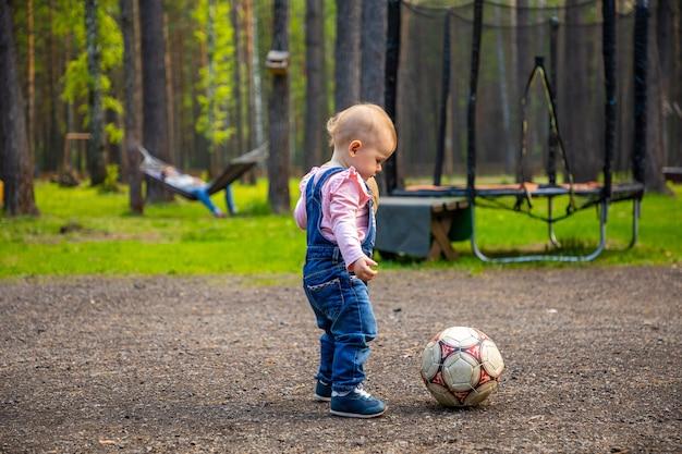 森のロシアでサッカーボールで遊ぶ小さなアクティブな女の子の赤ちゃんブロンド
