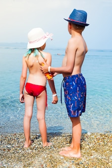 Little adorable boy with hat applying sun cream to his sister on the sea beach.
