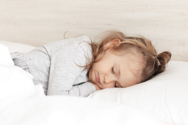 Little adorable child girl in grey pajamas closed eyes lying in bed sleeping on comfortable pillow and under white fluffy cotton blanket, good night sweet dreams