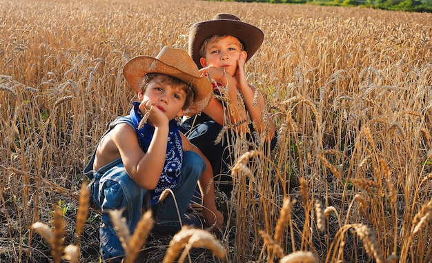 昼間に小麦畑に座っている小さな愛らしいカウボーイ