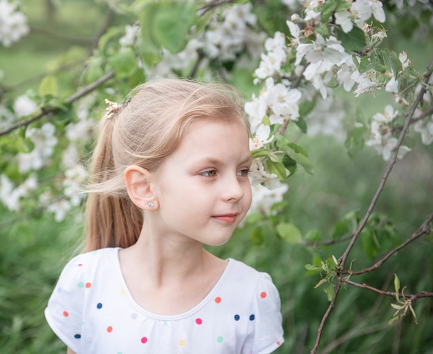 Little adorable girl  among the blossoming tree in apple garden