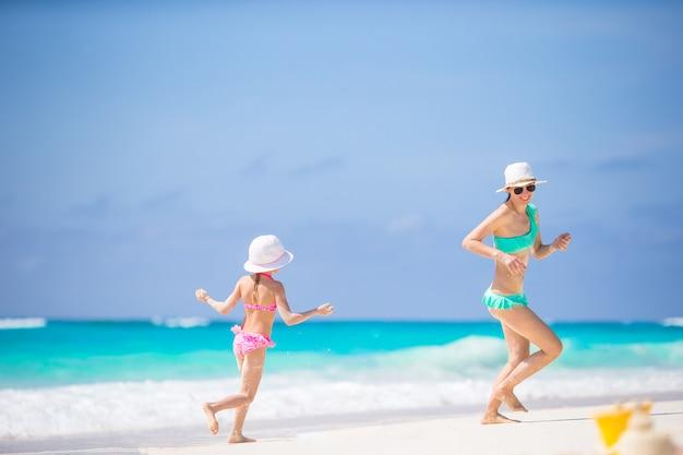 愛らしい少女と熱帯のビーチで楽しんで若い母親