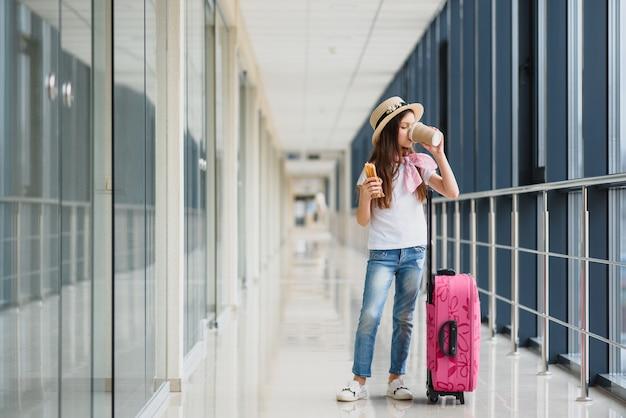 荷物を持って空港で愛らしい少女