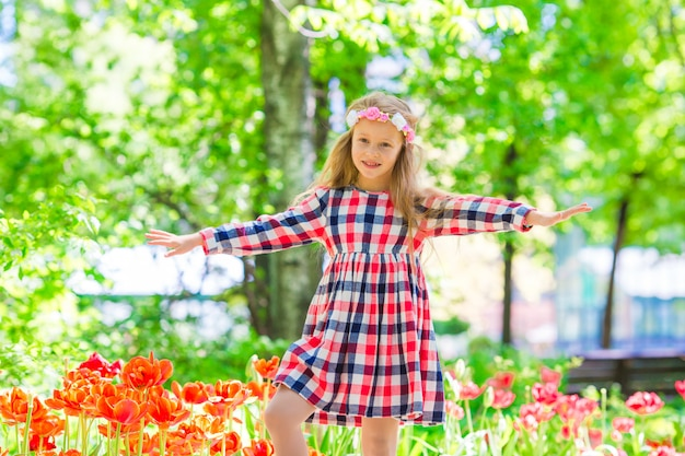Little adorable girl in blooming tulips garden. exhibition of different varieties of tulips in the park outdoors