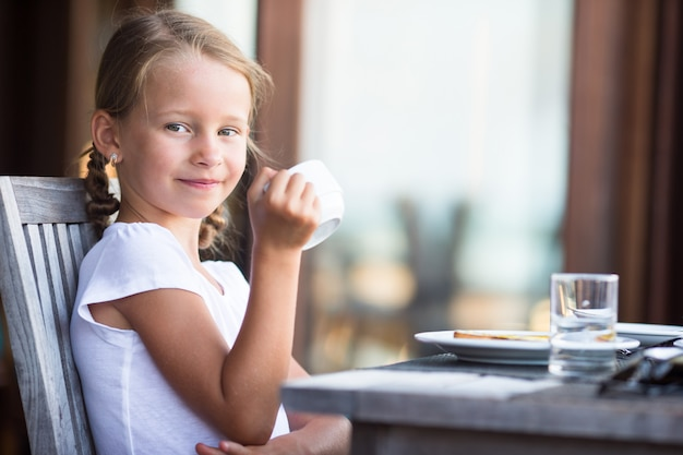 Little adorable girl drinking tea on breakfast in outdoor cafe