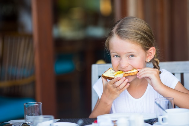 Little adorable girl eating bread with butter and honey on breakfast