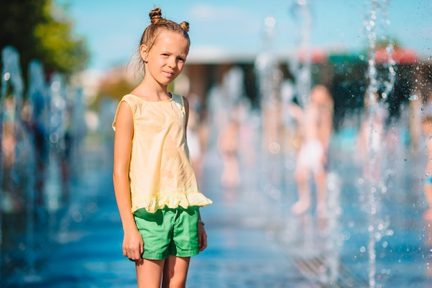 Little adorable girl have fun in street fountain at hot sunny day