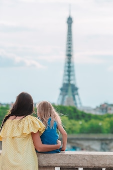 Little adorable girl and her young mom in paris near eiffel tower during summer vacation