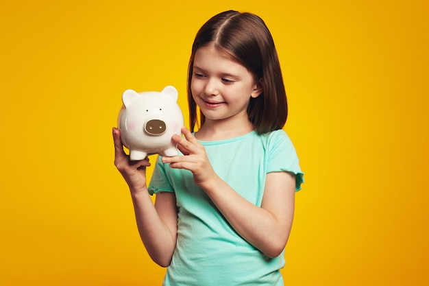 Little adorable girl holding money box in shape of pig near ear looking