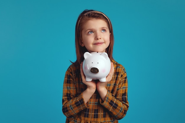 Little adorable girl holding money box in shape of pig near face looking up