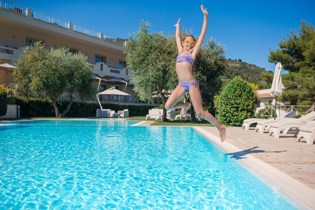 Little adorable girl jumping in the swimming pool