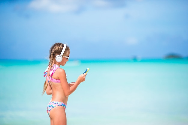 Little adorable girl listening music on the beach