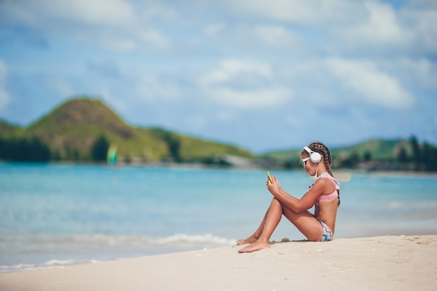 Little adorable girl listening music in the seashore