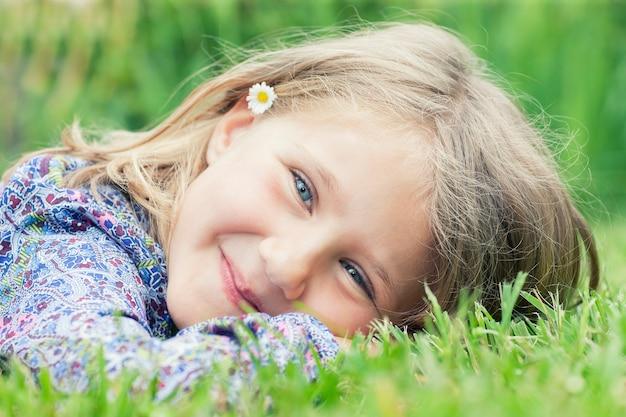 草の笑顔の上に横たわる愛らしい少女