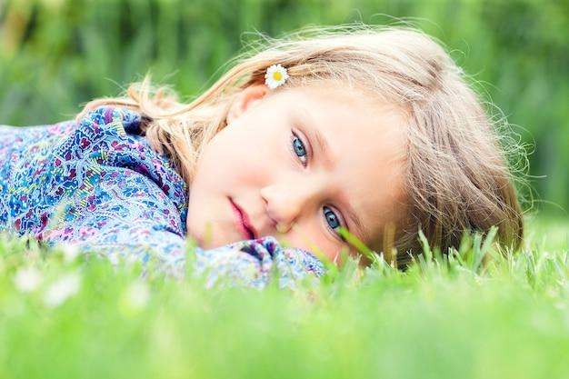 草の上に横たわっている小さな愛らしい女の子