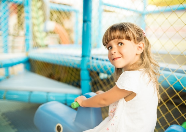 小さな愛らしい女の子がおもちゃの馬で遊ぶ