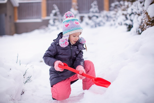 Little adorable girl play with snow shoveling on a winter day
