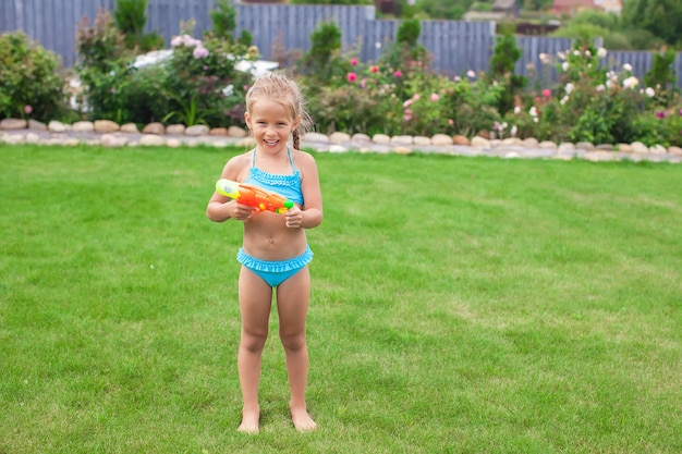 Little adorable girl playing with water gun outdoor in sunny summer day