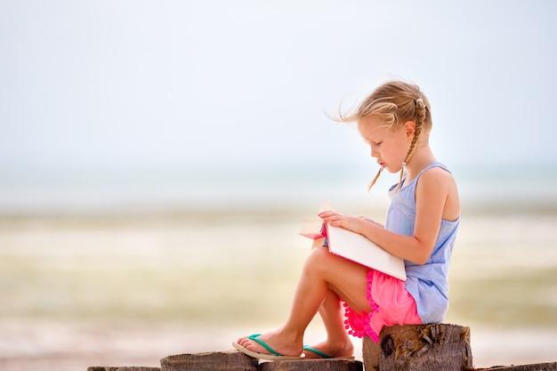 Little adorable girl reading book during tropical white beach