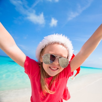 Little adorable girl in red santa hat have fun on the beach