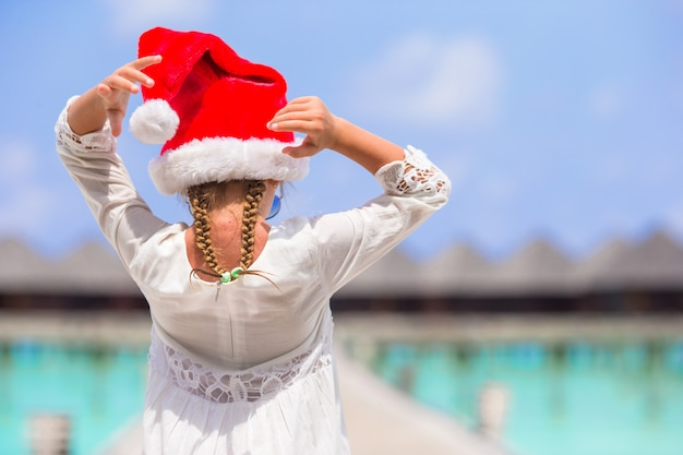 Little adorable girl in red santa hat on white beach