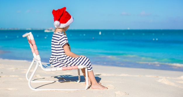 Little adorable girl in santa hat at tropical white beach