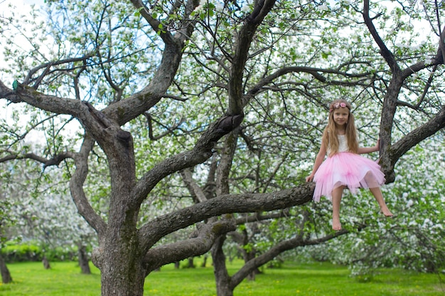 Little adorable girl sitting on blossoming apple tree