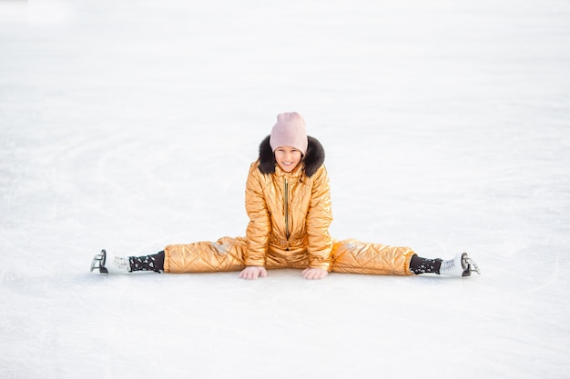 Little adorable girl sitting on ice with skates after fall