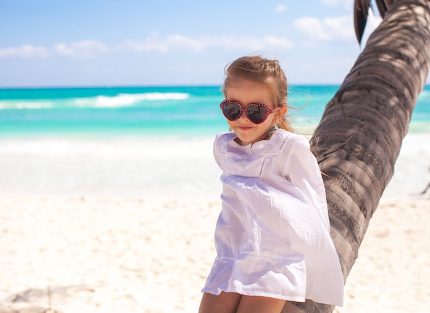 Little adorable girl sitting on palm tree at the perfect caribbean beach
