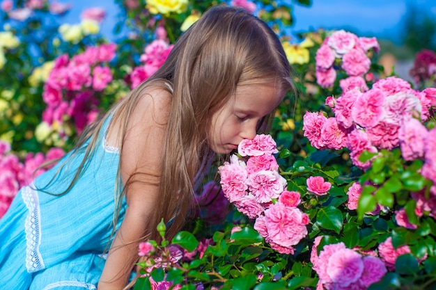 Little adorable girl smelling colorful flowers at summer day