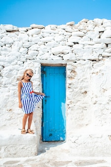 Little adorable girl at street of typical greek traditional village with white walls and colorful doors on mykonos island, in greece