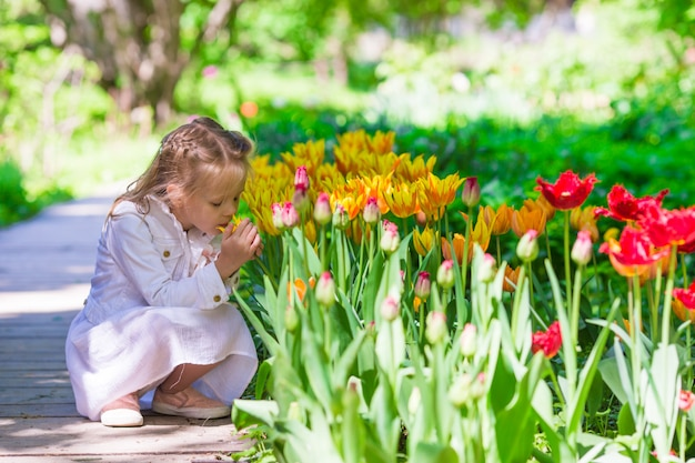 Little adorable girl in tulips garden at warm spring day