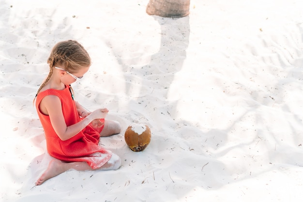 Little adorable girl with big coconut on sandy beach