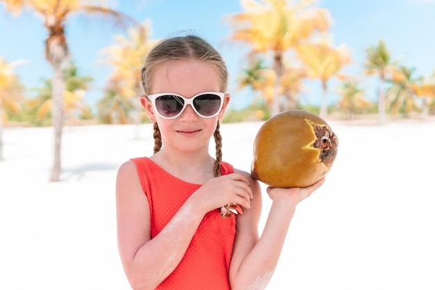 Little adorable girl with big coconut on sandy beach