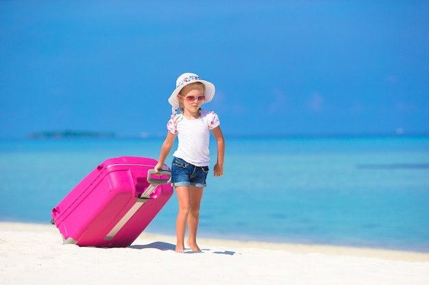 Little adorable girl with big suitcase on tropical white beach