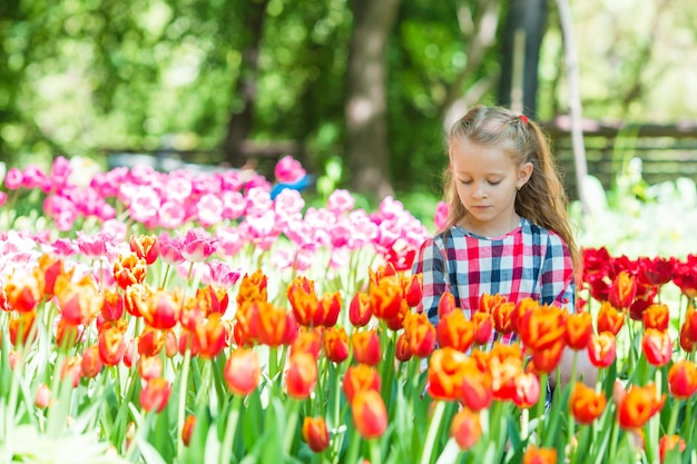 Little adorable girl with flowers in blooming tulips garden