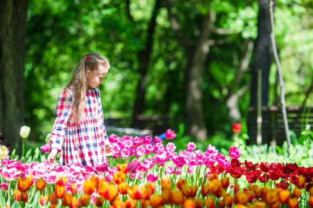 Little adorable girl with flowers in tulips garden