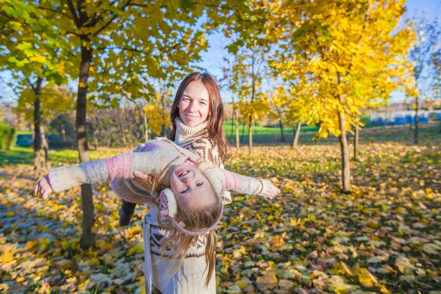 Little adorable girl and young mother having fun in autumn park on sunny day