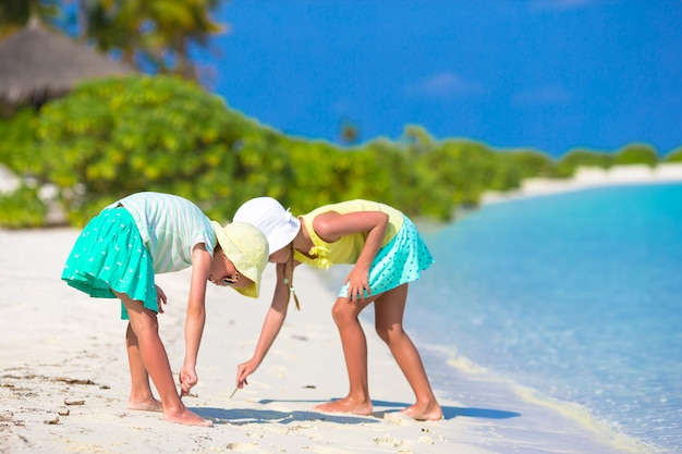 Little adorable girls drawing picture on white beach