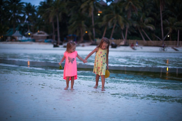 Little adorable girls in exotic resort in nice dress in the evening