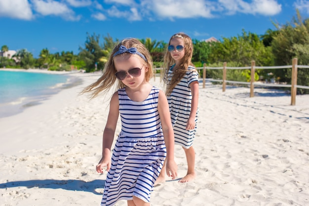Little adorable girls have fun on the beach