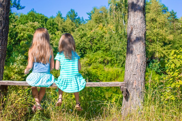 Little adorable girls outdoors at summer time