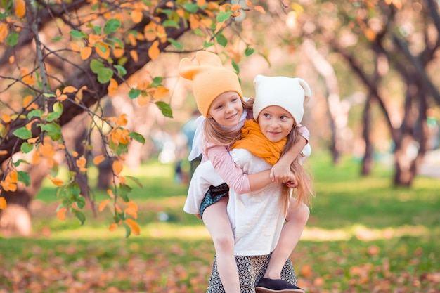 Little adorable girls outdoors at warm sunny autumn day
