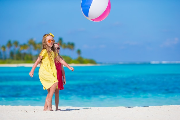 Little adorable girls playing on beach with ball